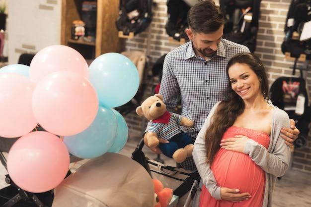 Uma mulher grávida junto com um homem escolher um carrinho de bebê