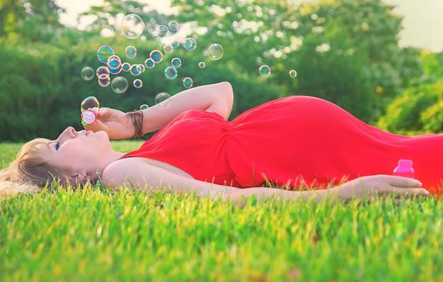 Uma mulher grávida sopra bolhas de sabão