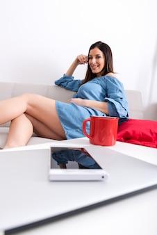 Uma mulher grávida sorridente, sentado em um sofá e coberto com um cobertor