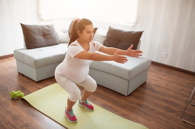 Uma mulher grávida trabalha em um tapete de ioga em casa. gravidez e esportes. yoga e pilates para mulheres grávidas. terceiro trimestre de gravidez