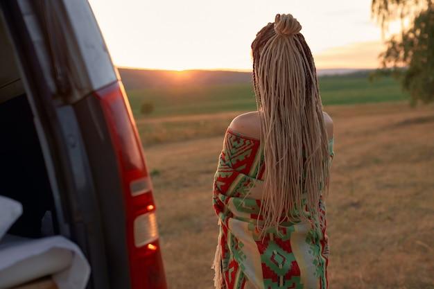 Uma mulher hippie com longos dreadlocks fica de costas para a câmera envolto em um vestido étnico brilhante.