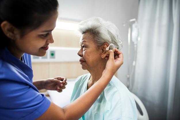 Uma mulher idosa com aparelho auditivo