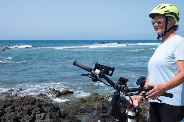 Uma mulher idosa com cabelos grisalhos, inclinando-se na bicicleta. céu azul e mar. aproveitando a atividade de bicicleta e para um estilo de vida saudável. ondas e rochas. motociclista feliz com óculos de sol e capacete amarelo