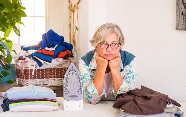 Uma mulher idosa com cabelos grisalhos triste porque muita roupa para passar, quarto doméstico com plantas e parede branca.