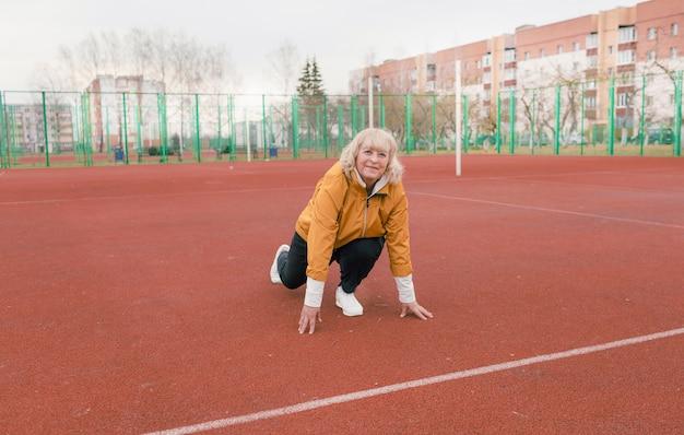 Uma mulher idosa com um casaco amarelo está fazendo exercícios em uma esteira vermelha. o estádio é um estilo de vida saudável. aposentados e esportes. velha ativa Foto Premium