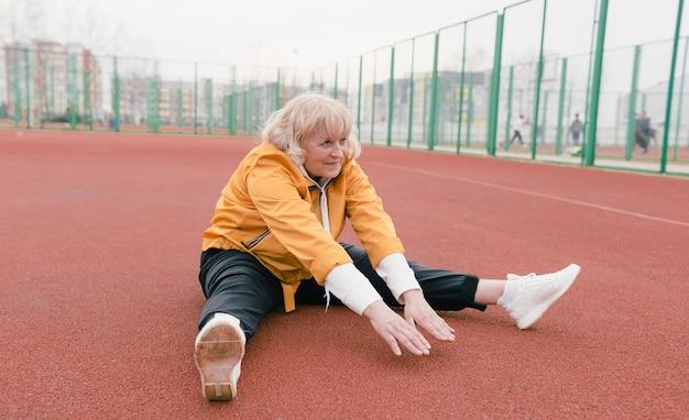 Uma mulher idosa com um casaco amarelo está fazendo exercícios em uma esteira vermelha. o estádio é um estilo de vida saudável. aposentados e esportes. velha ativa