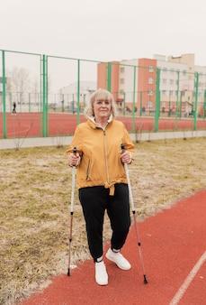 Uma mulher idosa com uma jaqueta amarela está com paus nórdicos nas mãos no estádio em uma esteira vermelha. estilo de vida saudável