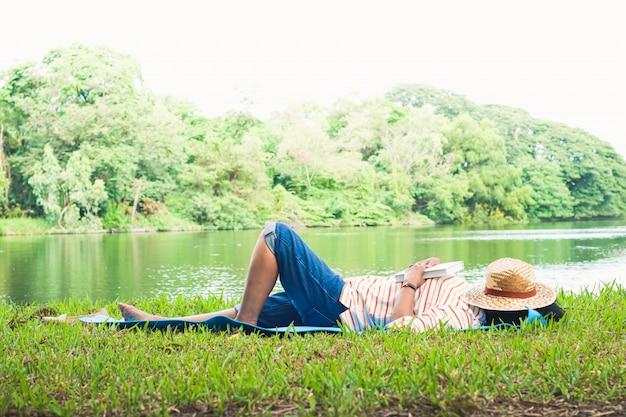 Uma mulher idosa dormiu lendo até dormir em um parque com um grande lago. vida feliz e simples na aposentadoria. conceito de comunidade sênior