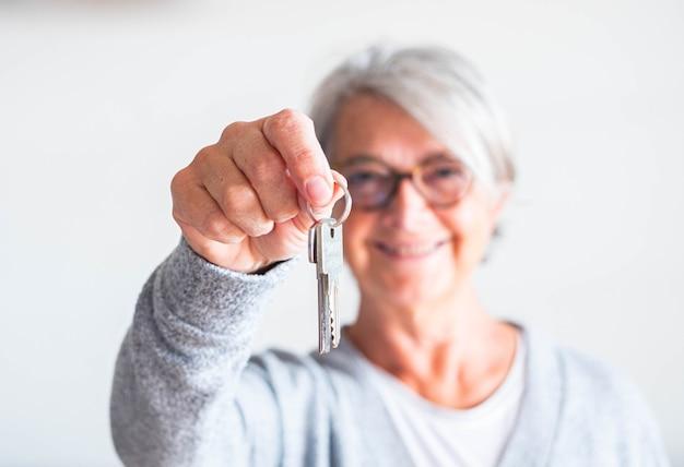 Uma mulher idosa e madura segurando a chave de uma casa ou carro - vende sua propriedade para alguém pronto para alugar ou comprar