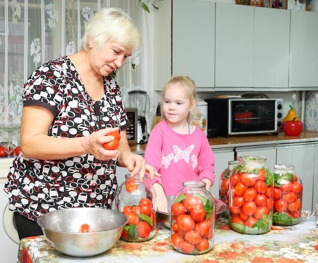 Uma mulher idosa e uma criança na cozinha preparando tomates em lata