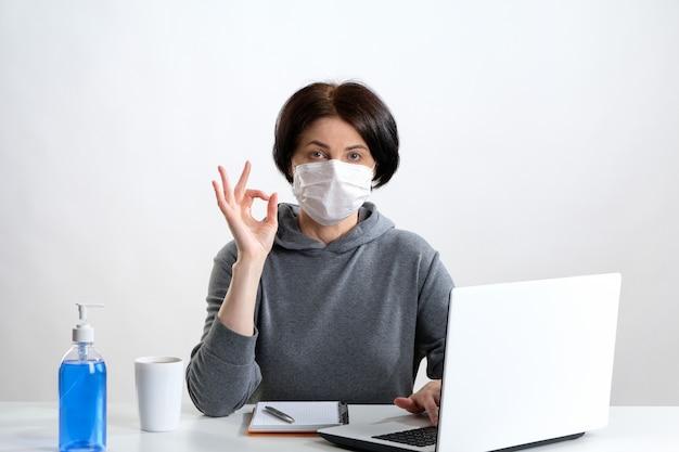 Uma mulher idosa em uma máscara protetora trabalha em um computador