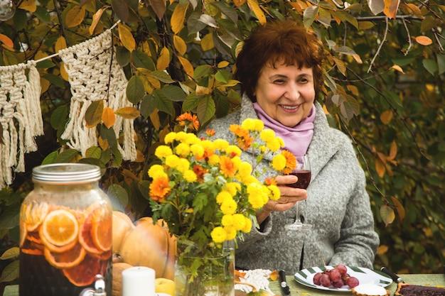 Uma mulher idosa em uma mesa festiva de outono em família sorri alegremente.