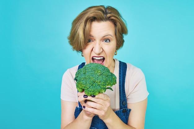 Uma mulher idosa está prestes a comer um prato vegetariano. mulher velha engraçada com uma dieta de brócolis.