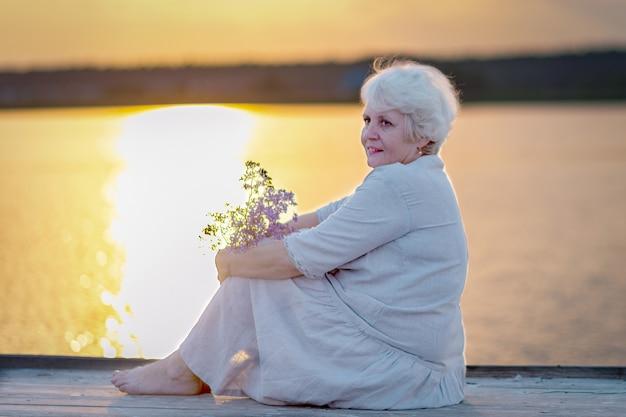 Uma mulher idosa está sentada no cais à beira do lago ao pôr do sol.