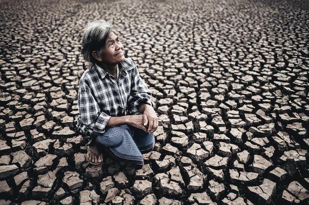 Uma mulher idosa está sentada olhando para o céu em tempo seco, o aquecimento global