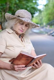 Uma mulher idosa lê um livro no parque