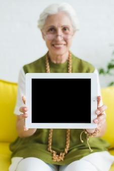 Uma mulher idosa mostrando tablet digital com tela em branco
