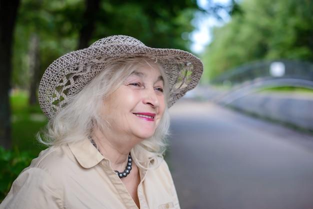 Uma mulher idosa no parque sorrindo