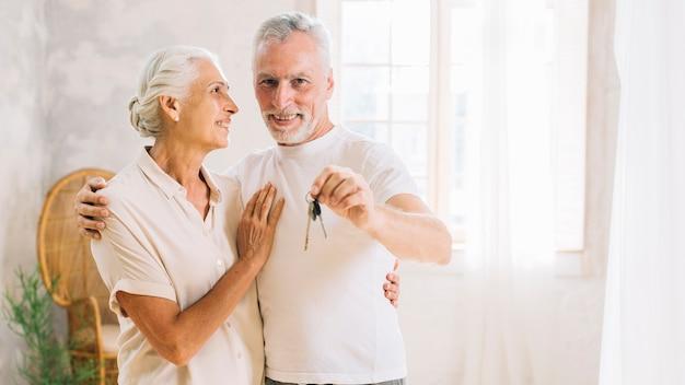 Uma mulher idosa olhando para o marido mostrando a chave da casa em casa