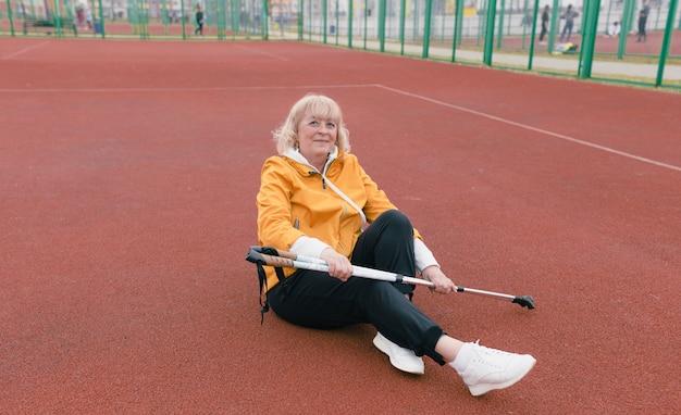 Uma mulher idosa se senta e descansa depois de um treino em uma esteira vermelha. varas escandinavas nas mãos. estilo de vida saudável.