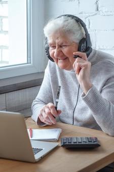 Uma mulher idosa se senta em uma mesa na frente de um laptop com fones de ouvido e escreve em um notebook.
