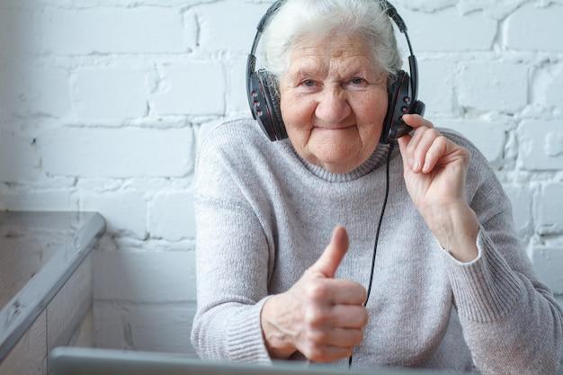 Uma mulher idosa se senta em uma mesa na frente de um laptop com fones de ouvido.