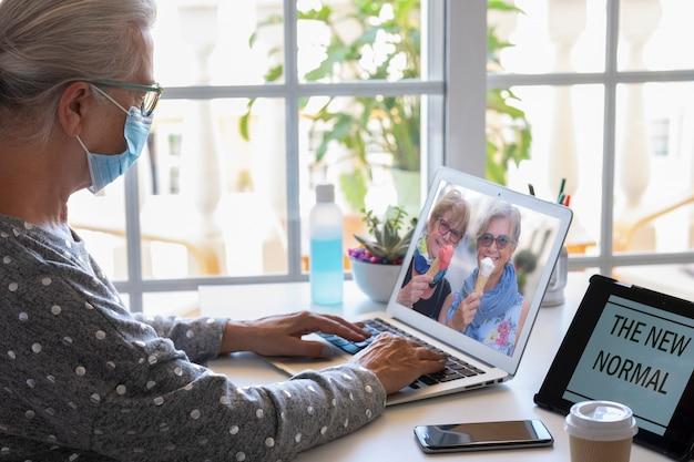 Uma mulher idosa sentada à mesa durante uma videochamada no laptop com um casal de amigas tomando um sorvete - conceito de felicidade e amizade à distância