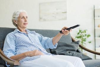 Uma mulher idosa sentada no sofá, mudando de canal com controle remoto