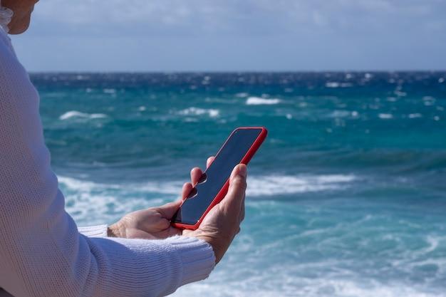Uma mulher idosa, vestida de branco, curtindo as férias na praia em um dia de vento, lendo uma mensagem no hsmartphone