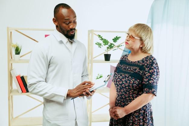 Uma mulher idosa visitando um terapeuta na clínica para obter uma consulta e verificar seu estado de saúde