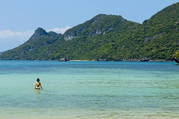 Uma mulher irreconhecível nadando no mar do parque nacional marinho de ang thong.