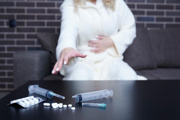 Uma mulher irreconhecível se senta no sofá e estende a mão para tomar um remédio