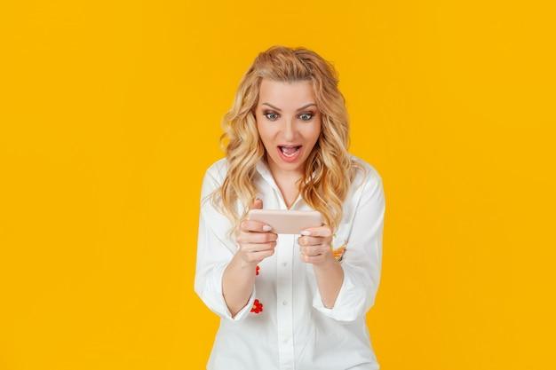 Uma mulher joga um novo jogo incrível para smartphones, grita de alegria e sorri, ganhando