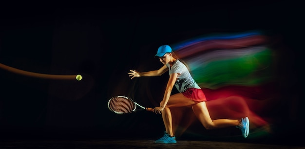 Uma mulher jogando tênis isolada em uma parede preta com luz mista e de stobe