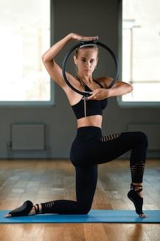 Uma mulher jovem, bonita e atlética faz exercícios com um anel de pilates no ginásio. mulher eslava de esportes em um terno preto.