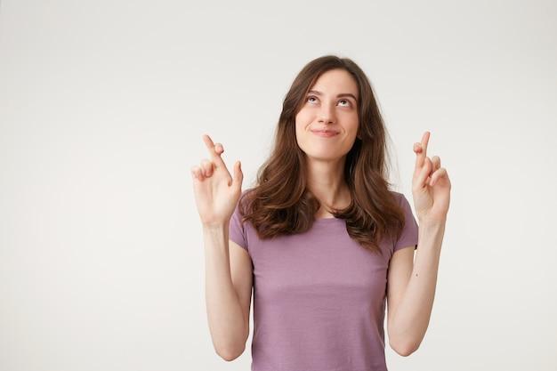 Uma mulher jovem, bonita e atraente com os dedos cruzados faz um pedido, reza por algo, olha para cima