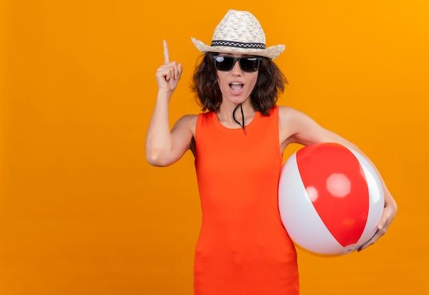 Uma mulher jovem com cabelo curto e camisa laranja, usando chapéu de sol e óculos escuros, segurando uma bola inflável apontando para cima com o dedo indicador