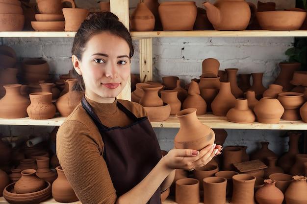Uma mulher jovem e alegre segurando um vaso de barro. o oleiro trabalha em uma oficina de olaria com barro. o conceito de maestria e criatividade em cerâmica.