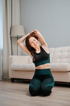 Uma mulher jovem e atraente faz ioga ou alongamento sentada no chão de um apartamento - conceito de um f ...