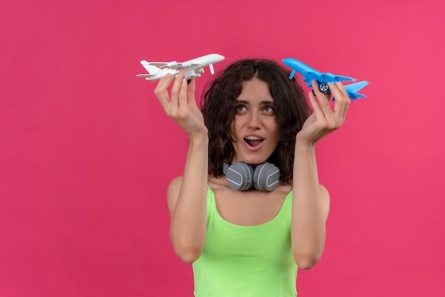 Uma mulher jovem e atraente feliz com cabelo curto em um top verde recortado em fones de ouvido segurando aviões de brinquedo azuis e brancos