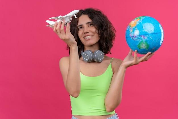 Uma mulher jovem e atraente feliz com cabelo curto em um top verde recortado em fones de ouvido segurando um globo e olhando para o avião de brinquedo