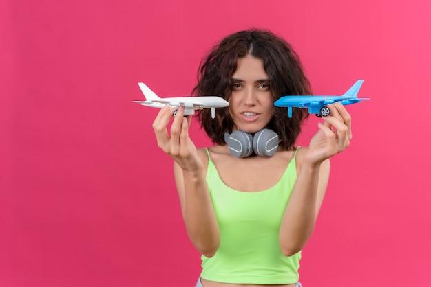 Uma mulher jovem e atraente, séria, com cabelo curto e top verde recortado em fones de ouvido segurando aviões de brinquedo azuis e brancos