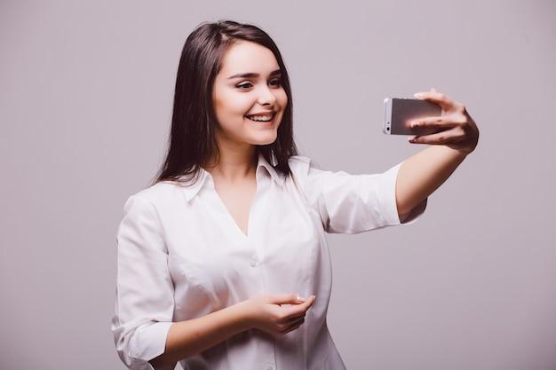Uma mulher jovem e atraente sorridente, segurando uma câmera digital com a mão e tirando um autorretrato de selfie, isolado no fundo branco.