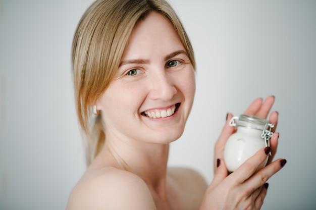 Uma mulher jovem e bonita com a pele limpa, fresca, tem um frasco branco com um creme facial isolado no fundo cinza.