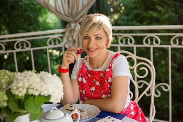 Uma mulher jovem e bonita comendo morangos. um buquê de flores brancas em uma mesa com verdes luxuriantes