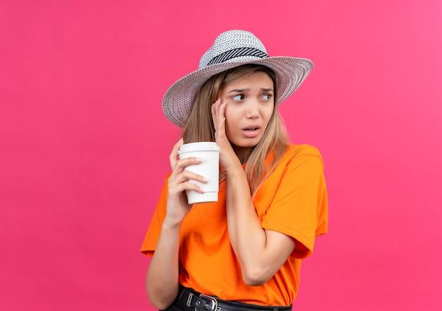 Uma mulher jovem e bonita confusa com uma camiseta laranja e chapéu de sol, olhando de lado, segurando um copo de plástico em uma parede rosa