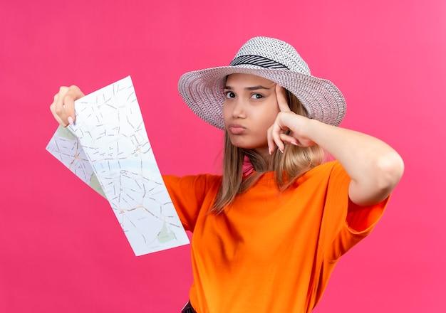 Uma mulher jovem e bonita confusa com uma camiseta laranja usando um chapéu de sol segurando o mapa enquanto aponta para a cabeça e olhando de lado em uma parede rosa