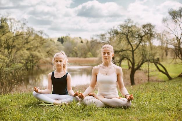 Uma mulher jovem e bonita e uma garota de cabelos louros estão meditando na posição de lótus.