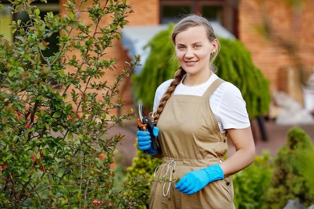 Uma mulher jovem e bonita em luvas de jardinagem está podando os galhos das plantas.