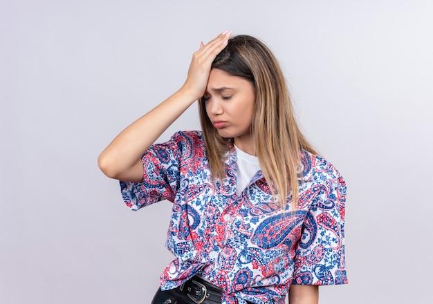 Uma mulher jovem e bonita estressante vestindo uma camisa estampada de paisley, mantendo as mãos na cabeça em uma parede branca